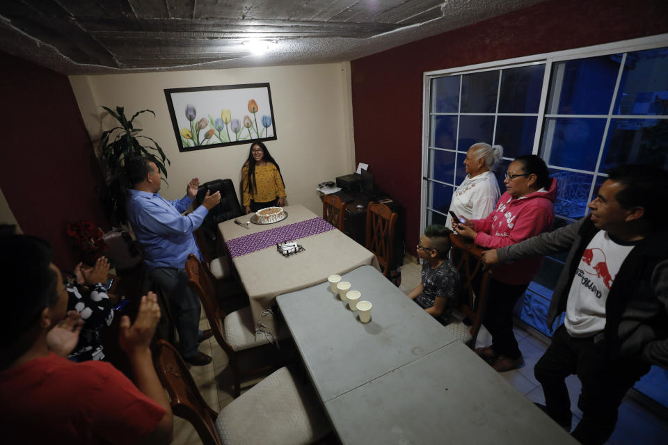"Family members clap as they sing ""Las Mananitas,"" Mexico's birthday song, to Ximena Canejo Hernandez, center, as they gather to mark her 15th birthday at home, in Tlalnepantla, just outside Mexico City, Monday, July 13, 2020. Ximena's family, wanting to give her a traditional Quinceanera, had booked a church and event hall for July 18th long before the coronavirus pandemic hit, but the celebration had to be postponed until late November. (AP Photo/Rebecca Blackwell)"
