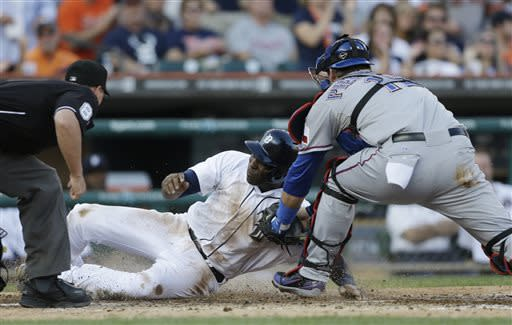 Umpire Quinn Wolcott, left, looks on as Detroit Tigers' Torii Hunter, center, scores under the tag of Texas Rangers catcher A.J. Pierzynski on Tigers' Victor Martinez's double to left field during the second inning of a baseball game in Detroit, Friday, July 12, 2013. (AP Photo/Carlos Osorio)