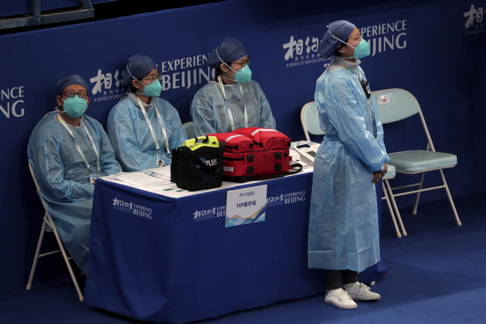 """Medical workers wearing face masks watch players compete in a curling competition during a test event for the 2022 Beijing Winter Olympics at National Aquatic Center, also known as the """"Water Cube"""" in Beijing, Thursday, April 1, 2021. Chinese capital hold a 10 days test events for 2022 Beijing Winter Olympics in five different venues from April 1-10, becomes the first city to hold both the Winter and Summer Olympics. (AP Photo/Andy Wong)"""