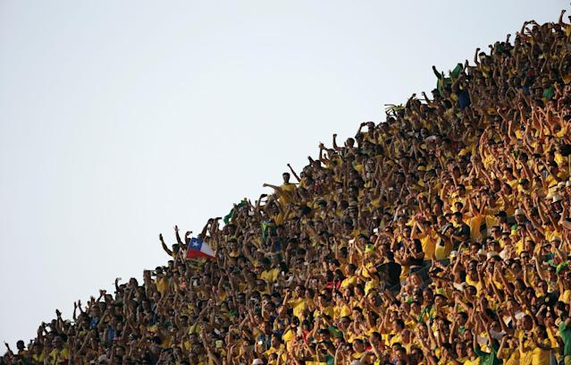 Fans cheer before the group A World Cup soccer match between Brazil and Croatia, the opening game of the tournament, in the Itaquerao Stadium in Sao Paulo, Brazil, Thursday, June 12, 2014. (AP Photo/Felipe Dana)