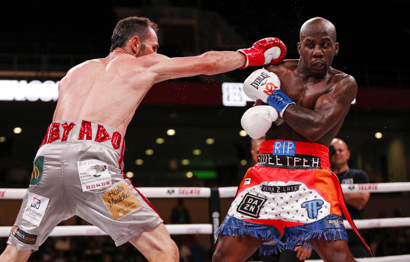 Tevin Farmer, right, dodges a punch from Guillaume Frenois during the fourth round of a boxing match, Saturday, July 27, 2019, in Arlington, Texas. Farmer won the 12 round match. (AP Photo/Brandon Wade)