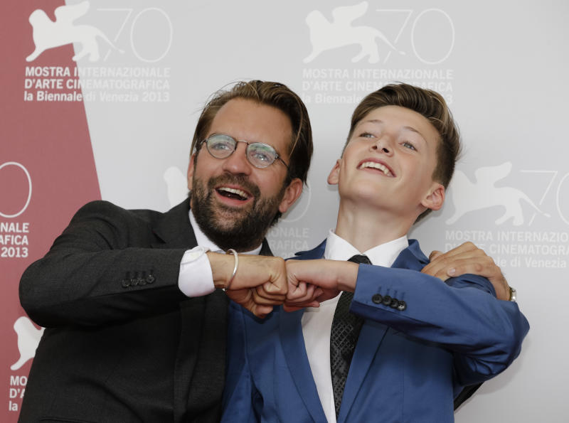 Director Rick Ostermann, left, poses with actor Levin Liam during the photo call for the movie 'Wolfschildren' at the 70th edition of the Venice Film Festival in Venice, Thursday, Aug. 29, 2013. (AP Photo/Andrew Medichini)