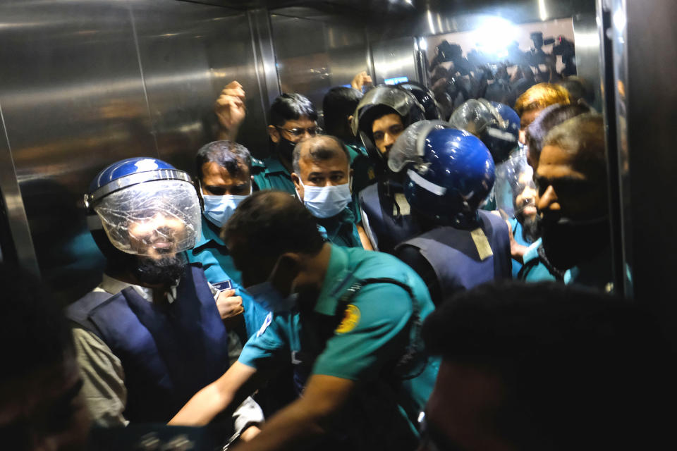 Police escort four of the eight suspected Islamist militants accused of the slayings of two men including a prominent gay rights activist five years ago, in an elevator as they head towards a court in Dhaka, Bangladesh, Tuesday, Aug. 31, 2021. The court sentenced six of them to death, lawyers said. On Tuesday, judge Mojibur Rahman of the Anti-Terrorism Special Tribunal said six were responsible for the killings of the two and acquitted two others. (AP Photo/Mahmud Hossain Opu)