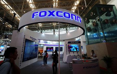 FILE PHOTO: Visitors are seen at a Foxconn booth at the World Intelligence Congress in Tianjin, China May 19, 2018. REUTERS/Stringe
