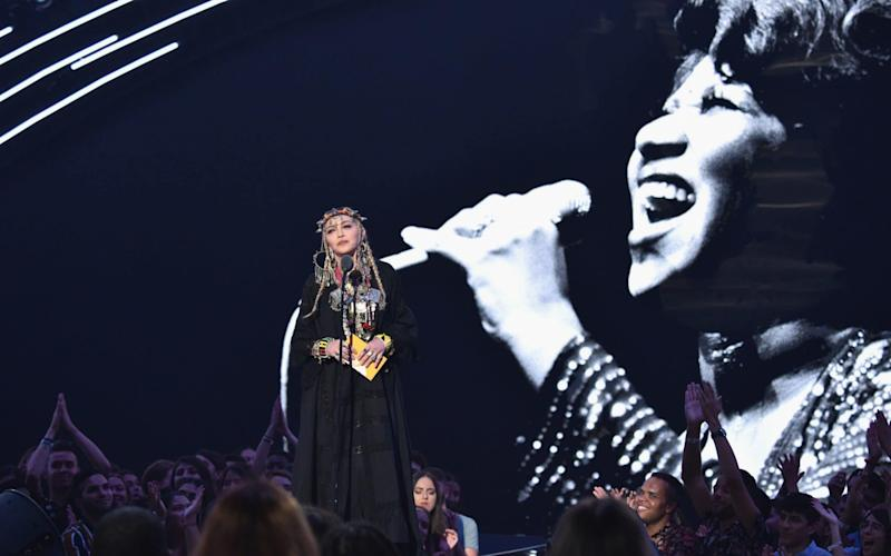 An enormous picture of Aretha Franklin is seen behind Madonna as she spoke of prostitution and crack-houses - Getty Images North America