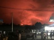 A general view shows civilians watching the smoke and flames of the volcanic eruption near Goma