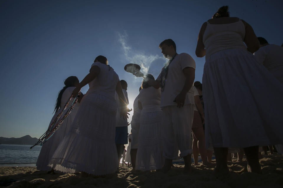 People gather on Praia Vermelha beach to make offerings to Yemanja, a deity from the Yoruba religion, as they honor the African goddess of the sea as part of New Year celebrations in Rio de Janeiro, Brazil, Tuesday, Dec. 31, 2019. As the year winds down, Brazilian worshippers of Yemanja celebrate the deity and ask for blessings for the coming year. (AP Photo/Bruna Prado)