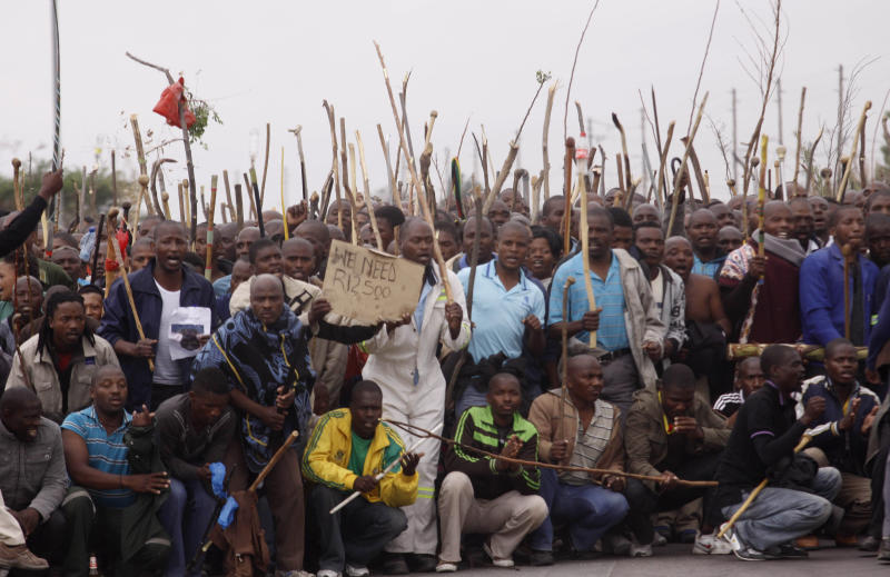 FILE- Striking mineworkers protest in Marikana, South Africa, in this file photo dated Wednesday Sept. 5, 2012.  The Anglo American Platinum mining company the world's largest platinum producer, announced Thursday Jan. 15, 2013, it will close four mine shafts and sell one mine, expecting to cut some 14,000 jobs only months after the country suffered massive labor unrest in the mining sector, while the government's minister of mines and the National Union of Mineworkers, NUM, expressed surprise and shock at the announcement. (AP Photo/Denis Farrell, File)