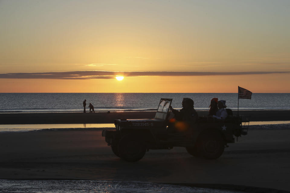 World War II reenactors drive a jeep at dawn on Omaha Beach in Saint-Laurent-sur-Mer, Normandy, Sunday, June 6, 2021, the day of 77th anniversary of the assault that helped bring an end to World War II. While France is planning to open up to vaccinated visitors starting next week, that comes too late for the D-Day anniversary. So for the second year in a row, most public commemoration events have been cancelled. (AP Photo/David Vincent)