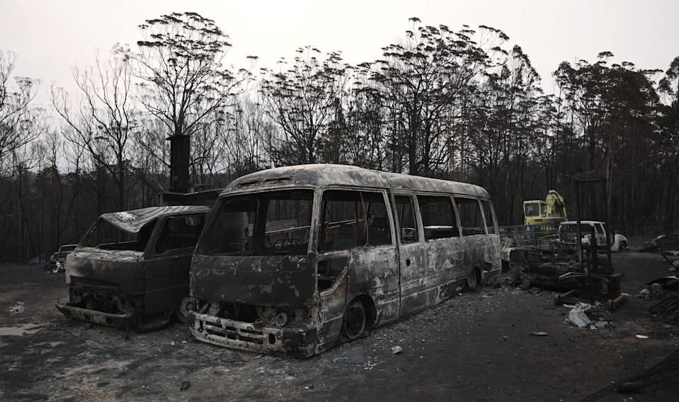 Vehicles gutted by bushfires are seen in the town of Lake Conjola in New South Wales on January 1, 2020. - A major operation to reach thousands of people stranded in fire-ravaged seaside towns was under way in Australia on January 1 after deadly bushfires ripped through popular tourist spots and rural areas leaving at least eight people dead. (Photo by PETER PARKS / AFP) (Photo by PETER PARKS/AFP via Getty Images)