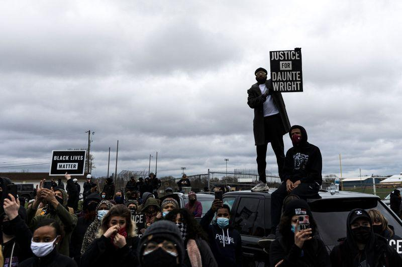 People gather holding signs and flags before curfew to protest the death of Daunte Wright who was shot and killed by a police officer in Brooklyn Center, Minnesota on April 12, 2021.
