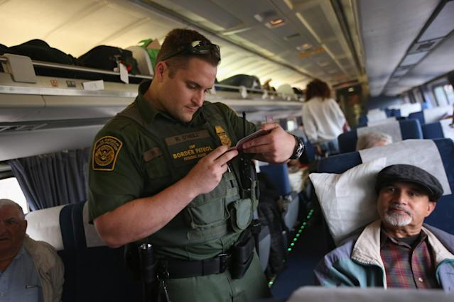 A U.S. Border Patrol agent checks passenger identifications aboard an Amtrak train from Chicago to New York City on June 5, 2013 in Depew, New York. The Border Patrol also monitors cross along the northern border between the United States and Canada. (Photo by John Moore/Getty Images)