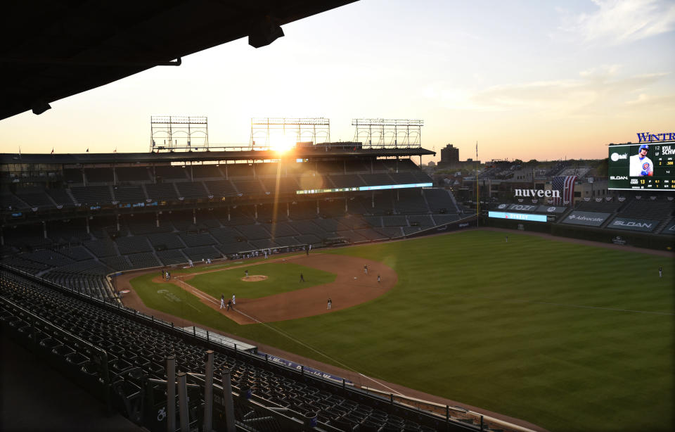 The sun sets behind Wrigley Field during the sixth inning of an opening day baseball game between the Chicago Cubs and the Milwaukee Brewers, Friday, July, 24, 2020, in Chicago. (AP Photo/David Banks)