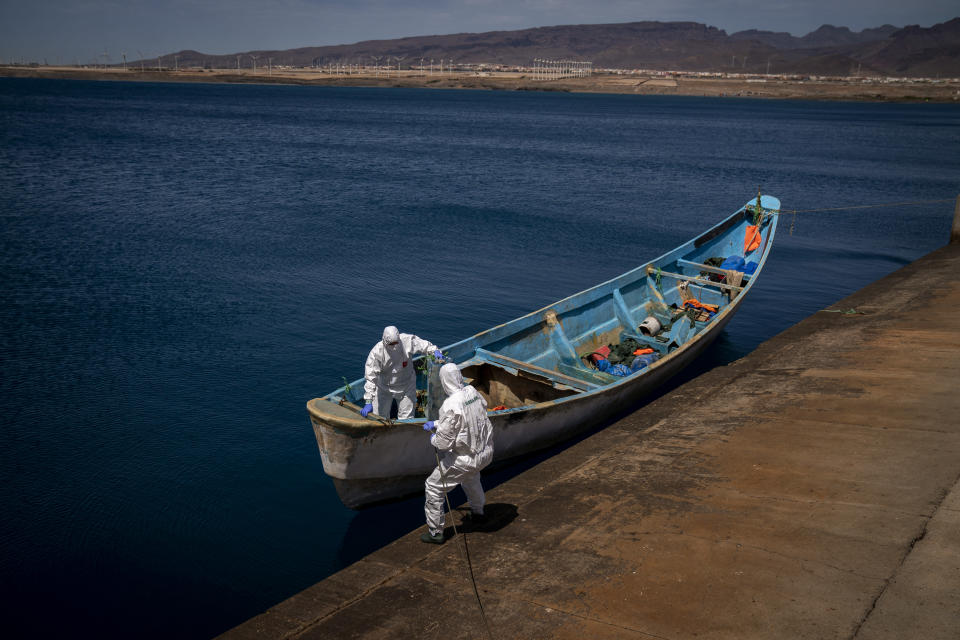 Police officers inspect a boat where 15 Malians were found dead adrift in the Atlantic on Thursday, Aug. 20, 2020 in Gran Canaria island, Spain. The 15 lifeless men were spotted inside a boat on Aug. 19 by a Spanish plane 80 nautical miles (148 kilometers, 92 miles) from the island of Gran Canaria. (AP Photo/Emilio Morenatti)