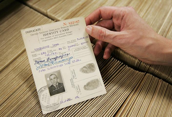 Picture taken on May 13, 2009 at the International Tracing Service (ITS) in Bad Arolsen shows a person holding the reproduction of documents including an identity card for John Demjanjuk, then known as Ivan, from the year 1948. (PATRICK SINKEL/AFP/Getty Images)