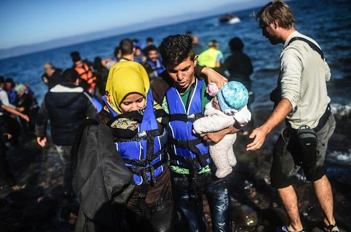 A young couple arrive with their baby on the Greek island of Lesbos after crossing the Aegean Sea from Turkey on November 12, 2015, en route to Europe (AFP Photo/Bulent Kilic)