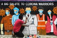 An Indian artist gives finishing touches to a mural depicting frontline workers during a day-long complete lockdown imposed in the eastern city of Kolkata