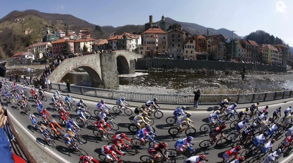 FILE - In this Saturday, March 21, 2009 file photo, the pack pedals by the town of Campo Ligure during the Milan-San Remo cycling classic in Italy. The impact of the Covid-19 virus on cycling has been escalating as Australian team Mitchelton-Scott decided to withdraw from racing until March 22. (AP Photo/Alessandro Trovati, File)