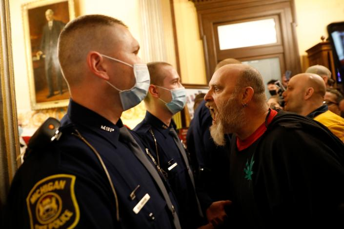 Protestors try to enter the Michigan House of Representatives chamber and are kept out by the Michigan State Police
