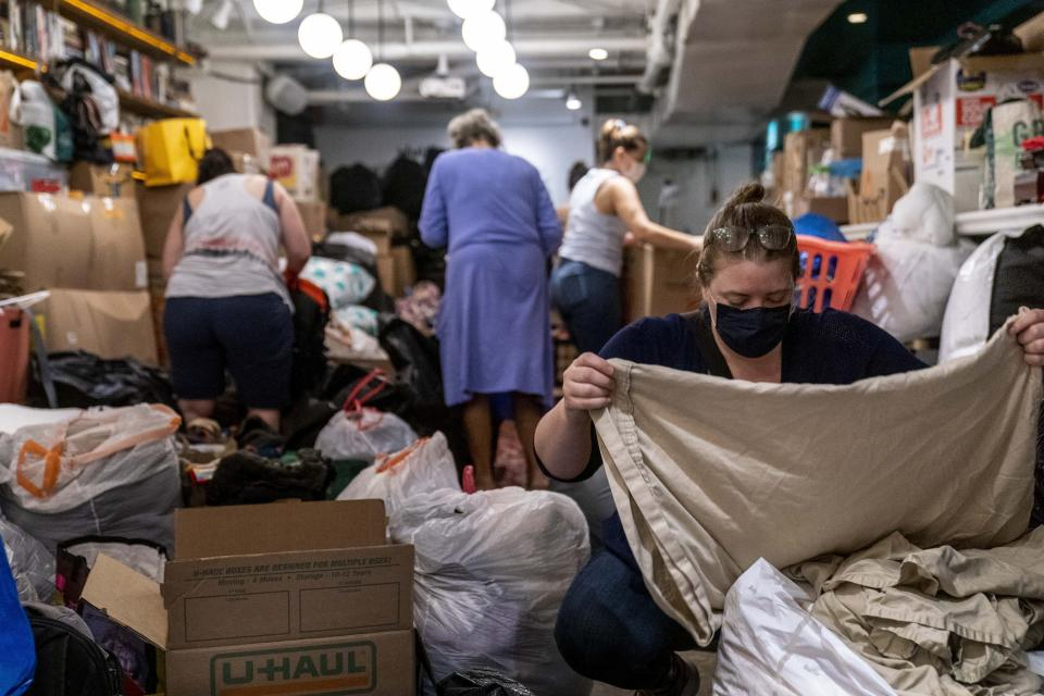Annie Osborn, right, and other volunteers, receive, sort, and pack thousands of items donated to refugees resettling in the Washington region who are fleeing Afghanistan at Lapis, an Afghani restaurant in Adams Morgan neighborhood of Washington, Thursday, Aug. 19, 2021. The restaurant, owned by an Afghan family, will be accepting an assortment of household items including toiletries, linens, kitchen supplies and more at two restaurants, Lapis and The Berliner, each weekday until Aug. 27 to give to refugees resettling in the Washington region who are fleeing Afghanistan. (AP Photo/Andrew Harnik)