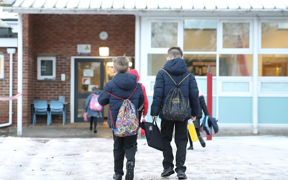 Pupils arrive at Manor Park School and Nursery in Knutsford, Cheshire, as schools across England return after the Christmas break. Boris Johnson has said parents should send primary-age children back to schools which remain open this week, despite growing calls from unions for them to close - Martin Rickett/PA Wire