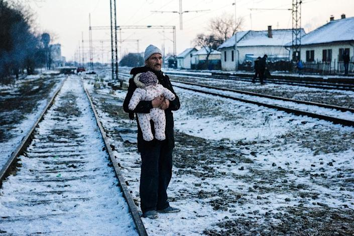 A man holds his baby while waiting with other migrants and refugees at a train station in southern Serbian town of Presevo on January 20, 2016 (AFP Photo/Dimitar Dilkoff)