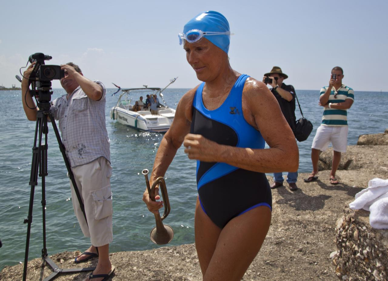U.S. swimmer Diana Nyad carries a trumpet before starting her swim in Havana, Cuba, Saturday, Aug. 18, 2012. Endurance athlete Nyad launched another bid Saturday to set an open-water record by swimming from Havana to the Florida Keys without a protective shark cage. (AP Photo/Ramon Espinosa)