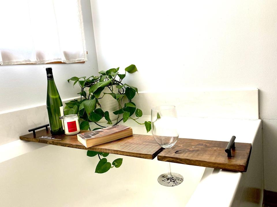 """<h2>The Crafty Hammer Bathtub Tray</h2><br>For the next best thing to a trip to the spa, get her this decorative tray — complete with a nifty slot for her wine glass — that is customizable to fit the dimensions of her very own bathtub. <br><br><br><em>Shop <strong><a href=""""https://www.etsy.com/listing/992443615/bathtub-tray-with-wine-holdero-wood-bath"""" rel=""""nofollow noopener"""" target=""""_blank"""" data-ylk=""""slk:Etsy"""" class=""""link rapid-noclick-resp"""">Etsy</a></strong></em><br><br><strong>TheCraftyHammer</strong> Bathtub Tray With Wine Holder, $, available at <a href=""""https://go.skimresources.com/?id=30283X879131&url=https%3A%2F%2Fwww.etsy.com%2Flisting%2F992443615%2Fbathtub-tray-with-wine-holdero-wood-bath"""" rel=""""nofollow noopener"""" target=""""_blank"""" data-ylk=""""slk:Etsy"""" class=""""link rapid-noclick-resp"""">Etsy</a>"""