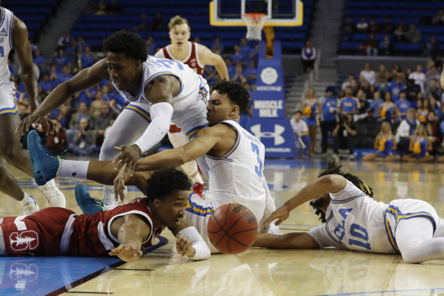 Stanford guard Bryce Wills, bottom, vies for a loose ball with UCLA guard David Singleton, top, guard Jules Bernard (3) and guard Tyger Campbell (10) during the first half of an NCAA college basketball game in Los Angeles, Wednesday, Jan. 15, 2020. (AP Photo/Chris Carlson)