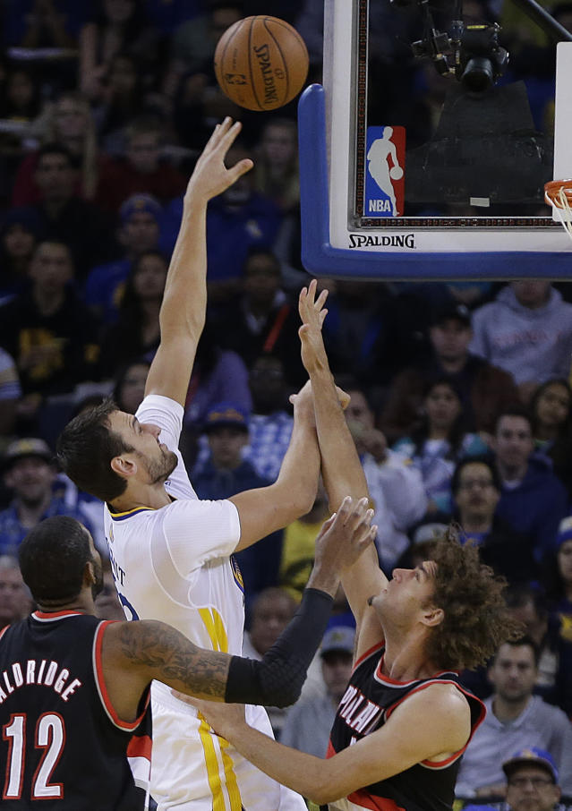 Golden State Warriors' Andrew Bogut, center, shoots over Portland Trail Blazers' Robin Lopez, right, and LaMarcus Aldridge (12) during the first half of an NBA basketball game Saturday, Nov. 23, 2013, in Oakland, Calif. (AP Photo/Ben Margot)