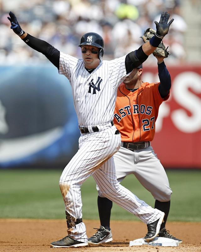 New York Yankees' Martin Prado raises his arms to signal safe on a second-inning double as Houston Astros relief pitcher Jesse Crain (26) stands on the base behind him in a baseball game at Yankee Stadium in New York, Thursday, Aug. 21, 2014. (AP Photo/Kathy Willens)