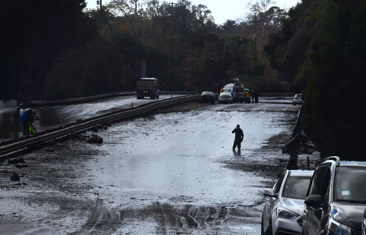 <p>A man wades in a flooded section of the US 101 freeway near the San Ysidro exit in Montecito, California on Jan. 9, 2018.<br /> (Photo: Frederic J. Brown/AFP/Getty Images) </p>