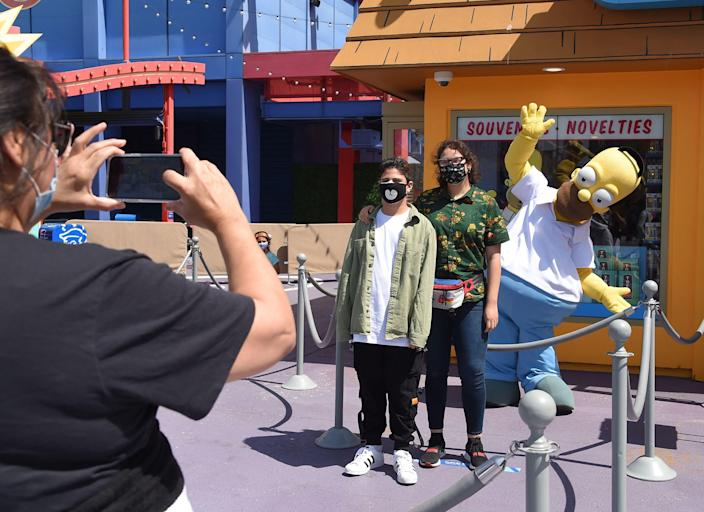 Guests pose with Homer Simpson on the opening day for season and annual pass holders of Universal Studios in Los Angeles on April 15, 2021.