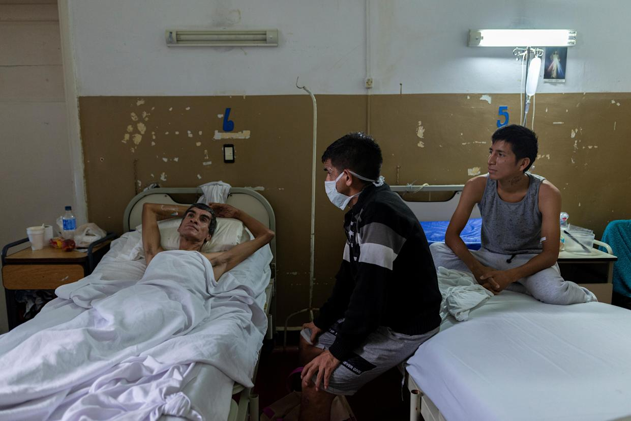 Lucas, center, a former tuberculosis patient, visits patients Jorge, left, and Arturo Maldonado, who have both been hospitalized for tuberculosis in Muniz public hospital in Buenos Aires, Argentina, Jan. 25, 2019. (Photo: Magali Druscovich/Reuters)