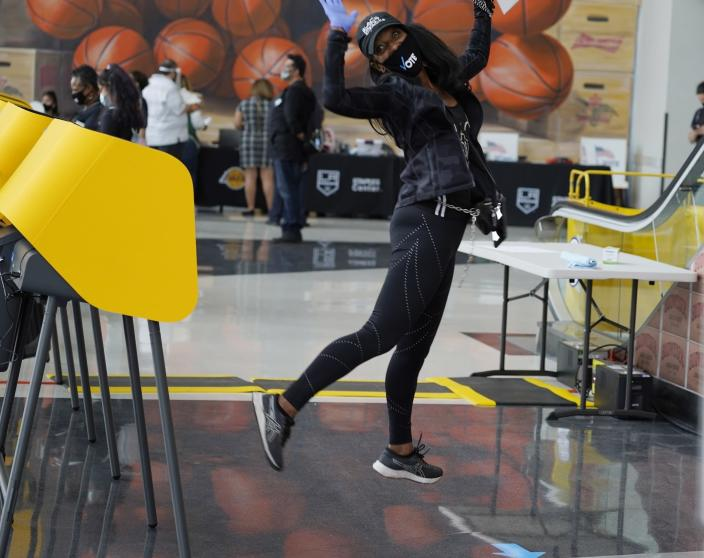 FILE - In this Saturday, Oct. 24, 2020, file photo, Debra Hubbard jumps after voting on the first day of early voting inside the Vote Center at Staples Center sports and entertainment arena in Los Angeles. Tens of millions of Americans already cast ballots in the 2020 election amid record-breaking early voting during the coronavirus pandemic. But for some voters in a handful of states, casting an early ballot in-person isn't even an option. (AP Photo/Damian Dovarganes, File)