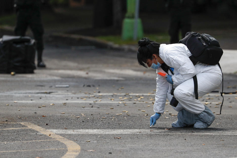 A forensic investigator collects cartridges at the scene where the Mexican capital's police chief was attacked by gunmen in Mexico City, Friday, June 26, 2020. Heavily armed gunmen attacked and wounded Omar García Harfuch in an operation that left several dead. (AP Photo/Rebecca Blackwell)