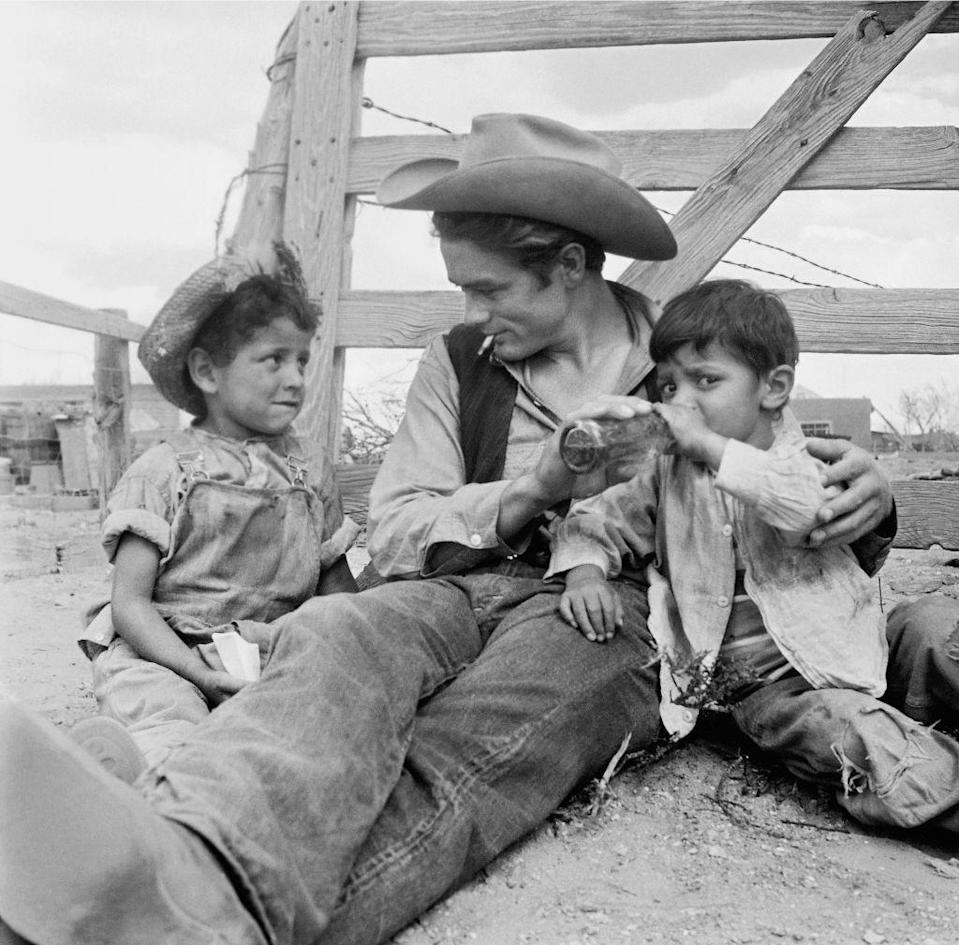 <p>Dean is seen tending to two small children while on set of <em>Giant. </em></p>
