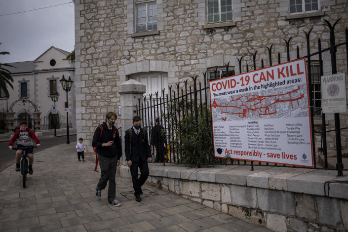 """Schoolchildren walk by a COVID-19 informative banner in Gibraltar, Thursday, March 4, 2021. Gibraltar, a densely populated narrow peninsula at the mouth of the Mediterranean Sea, is emerging from a two-month lockdown with the help of a successful vaccination rollout. The British overseas territory is currently on track to complete by the end of March the vaccination of both its residents over age 16 and its vast imported workforce. But the recent easing of restrictions, in what authorities have christened """"Operation Freedom,"""" leaves Gibraltar with the challenge of reopening to a globalized world with unequal access to coronavirus jabs. (AP Photo/Bernat Armangue)"""