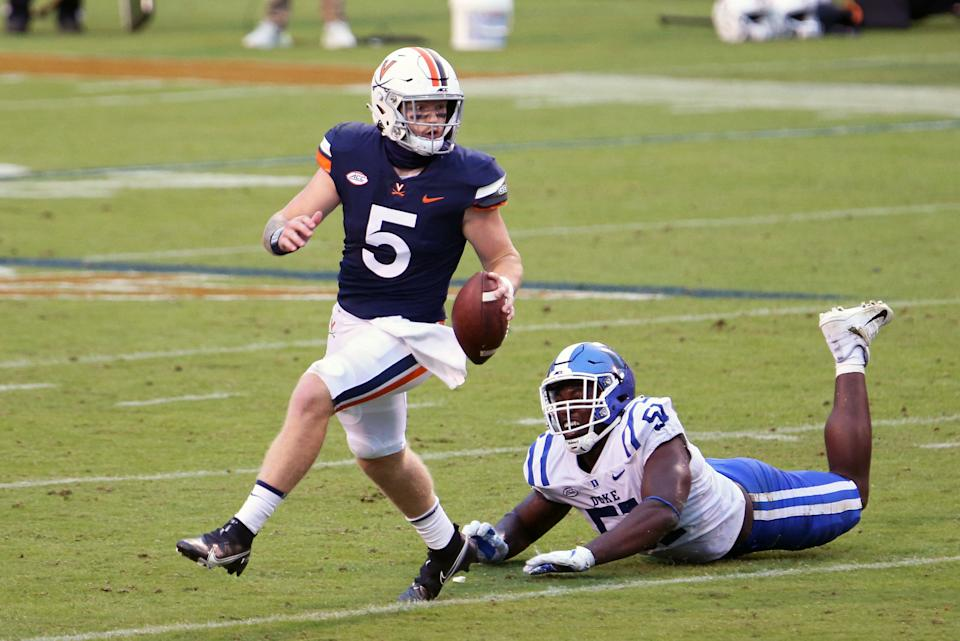 CHARLOTTESVILLE, VA - SEPTEMBER 26: Brennan Armstrong #5 of the Virginia Cavaliers scrambles away from Victor Dimukeje #51 of the Duke Blue Devils in the second half during a game on September 26, 2020 in Charlottesville, Virginia. (Photo by Ryan M. Kelly/Getty Images)