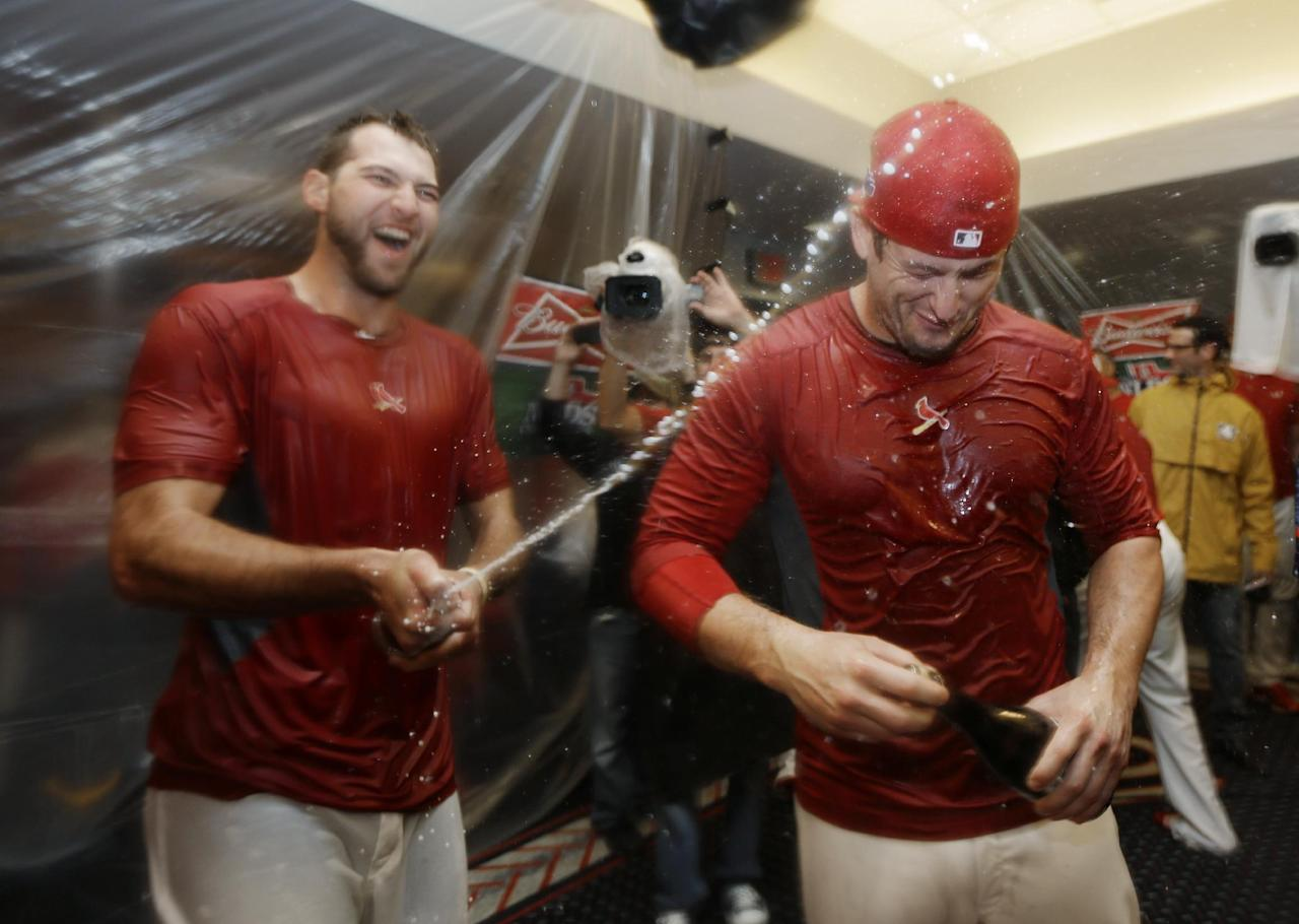 St. Louis Cardinals' Michael Wacha, left, sprays David Freese, right, after the Cardinals defeated the Pittsburgh Pirates 6-1 in Game 5 in a National League baseball division series, Wednesday, Oct. 9, 2013, in St. Louis. The Cardinals advanced to the NL championship series against the Los Angeles Dodgers.  (AP Photo/Jeff Roberson)