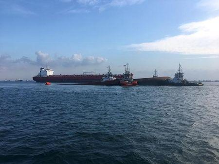 Tug boats move a partially submerged Dominican-registered dredger safely into an area after a collision with an Indonesian-registered tanker in Singapore's territorial waters near Pulau Senang