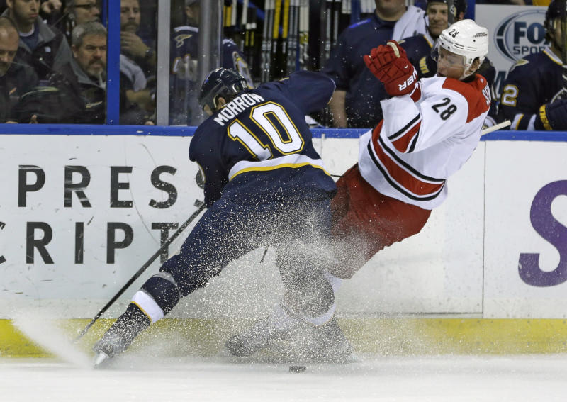 Carolina Hurricanes' Alexander Semin, of Russia, slips as he chases after a loose puck along side St. Louis Blues' Brenden Morrow, left, during the first period of an NHL hockey game Saturday, Nov. 16, 2013, in St. Louis. (AP Photo/Jeff Roberson)