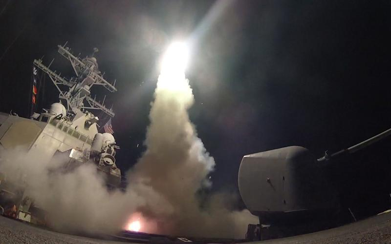 "Undated handout photo issued by the US Navy of USS Porter (DDG 78) firing a tomahawk land attack missile from the Mediterranean Sea, as Britain backed the US missile strike on a Syrian air base as an ""appropriate response"" to Bashar Assad regime's ""barbaric"" chemical attack. - Credit: Seaman Ford Williams/US Navy/PA"