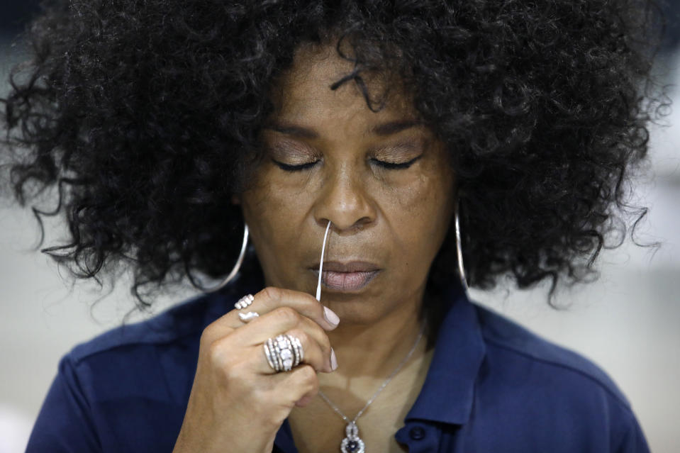 Rustye Barzoni Covington swabs her nose while giving a coronavirus test to herself during a tour of setup at a temporary coronavirus testing site Monday, Aug. 3, 2020, in Las Vegas. (AP Photo/John Locher)