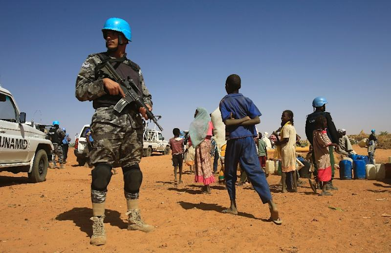 Sudanese people walk past a member of the UN-African Union mission in Darfur at the Zam Zam camp for Internally Displaced People in Sudan on April 9, 2015