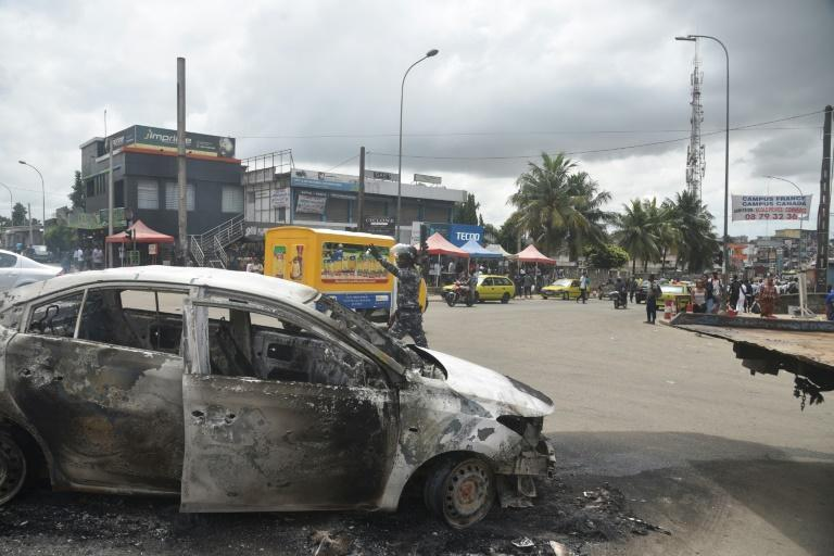 A policeman gestures next to a car in Abidjan's Cocody district that was torched in anti-Ouattara protests on October 19