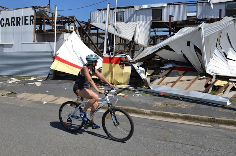 A resident cycles past a cyclone-damaged business in the northern Queensland town of Rockhampton on February 21, 2015 (AFP Photo/Peter Parks)