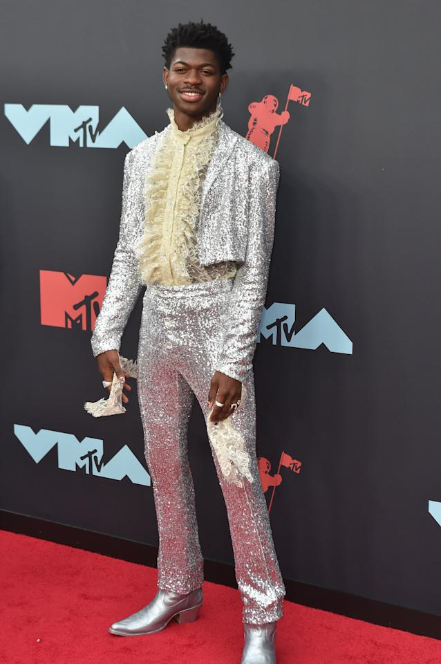 <p>Lil Nas X is not one to shy away from experimenting with fashion and he did just that when he arrived on the red carpet of the 2019 Video Music Awards.</p> <p><strong>What to wear:</strong> Glittery silver jacket and pants and high-collared ruffled white shirt.</p>