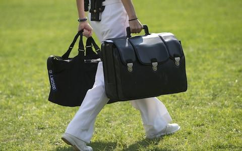 "A White House military aide and member o...A White House military aide and member of the US Navy carries a briefcase known as the ""football,"" containing emergency nuclear weapon codes in 2012 - Credit:  SAUL LOEB/AFP"