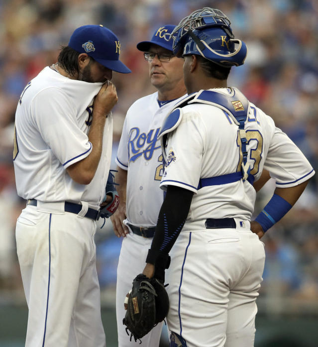 Kansas City Royals starting pitcher Jason Hammel, left, talks with pitching coach Cal Eldred, back, and catcher Salvador Perez (13) during the second inning of the team's baseball game against the Boston Red Sox at Kauffman Stadium in Kansas City, Mo., Friday, July 6, 2018. The Red Sox scored eight runs in the first two innings. (AP Photo/Orlin Wagner)